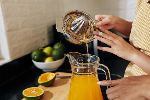 Kobieta nalewa sok do słoika