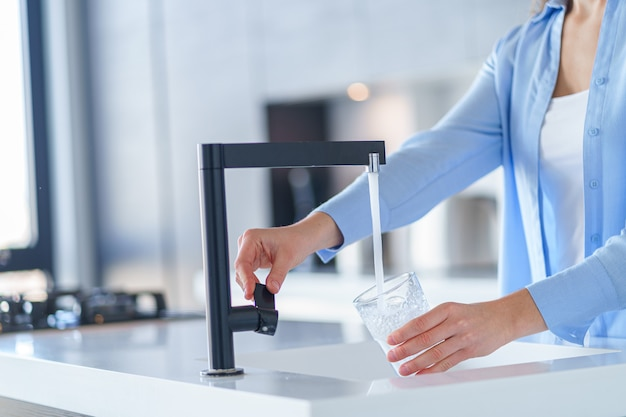 Kobieta nalewa świeżo przefiltrowaną oczyszczoną wodę z kranu do szklanki w kuchni w domu