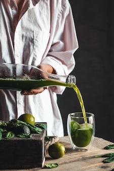 Kobieta nalewa świeżo zmieszane zielone i białe smoothie do szklanego słoika ze składnikami na rustykalnym drewnianym stole