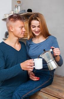 Kobieta nalewa swojemu chłopakowi kawę