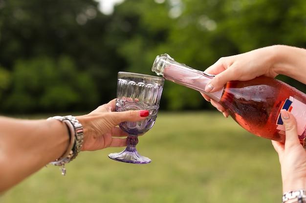 Kobieta nalewa szampana w kieliszkach na piknik pary.