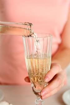 Kobieta nalewa wino do szkła, z bliska