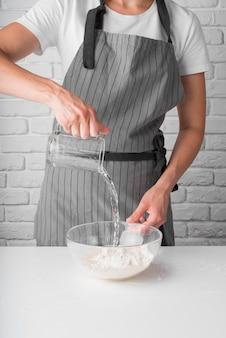 Kobieta nalewa wodę do miski