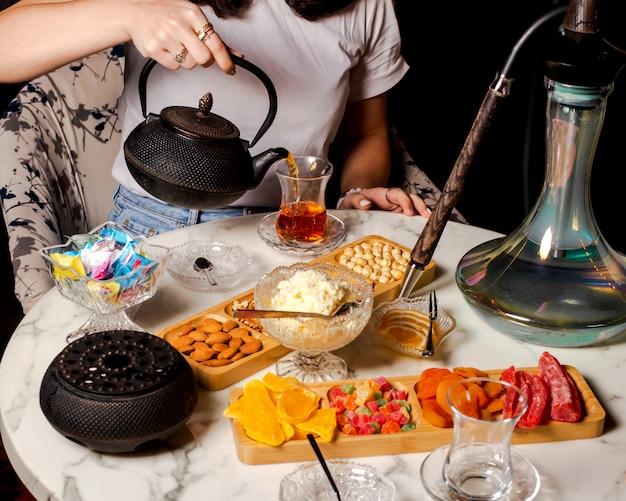 Kobieta nalewająca czarną herbatę do szklanki w kształcie gruszki serwowana przy ustawieniu herbaty