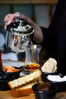Kobieta nalewania herbaty w szkle