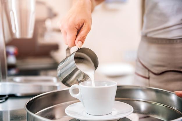 Kobieta nalewania mleka w kawie