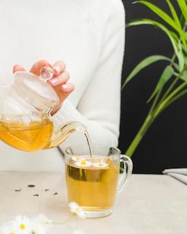 Kobieta nalewanie herbaty z kryształowy czajniczek