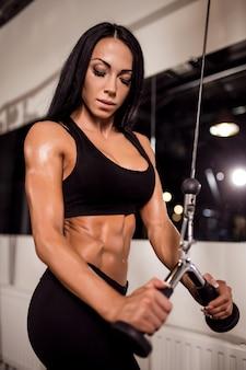 Kobieta napina mięśnie na kablowej maszynie w gym
