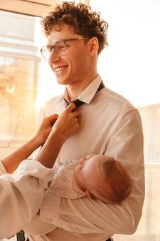 Kobieta naprawia krawat uśmiechniętych mężów, gdy trzyma swojego synka, stoi w domu, szykując się do pracy