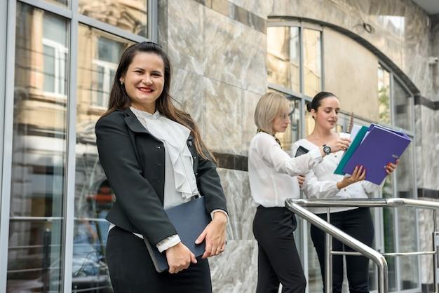 Kobieta naprzeciw swoich kolegów pokazuje informacje na tablecie, kolejne dwie stoją z tyłu