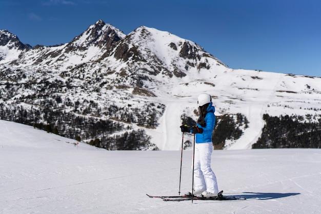 Kobieta narciarz korzystających z spokojnej i pogodnej zimowej panoramy w grandvalira, andora