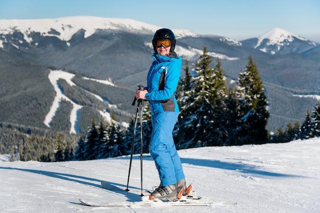 Kobieta narciarz na stoku w ośrodku narciarskim w zimie