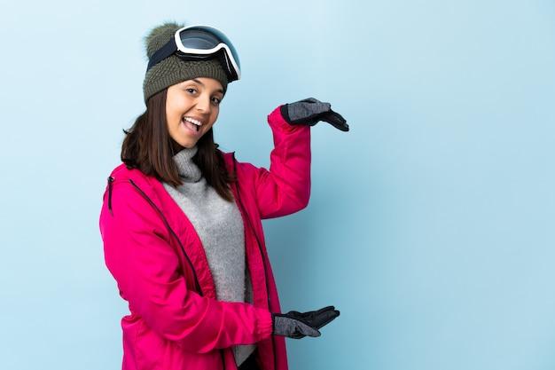 Kobieta narciarz rasy mieszanej w okularach snowboardowych na pojedyncze niebieskie ściany gospodarstwa copyspace, aby wstawić reklamę
