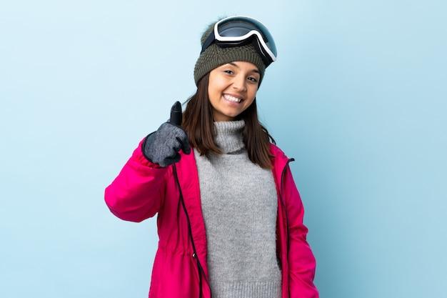 Kobieta narciarz rasy mieszanej z okularami snowboardowymi na pojedyncze niebieskie miejsce z kciuki do góry, ponieważ stało się coś dobrego