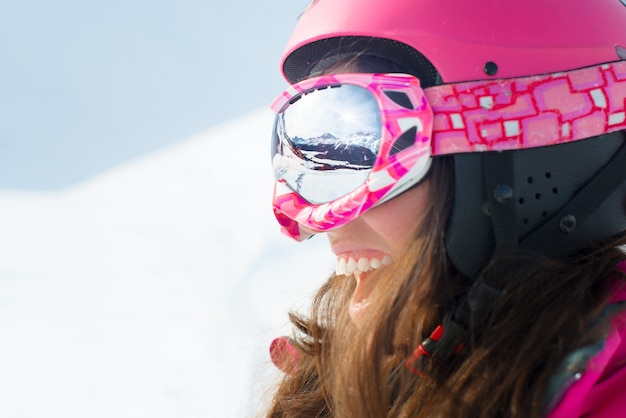 Kobieta narciarz uśmiecha się i nosi okulary narciarskie z nart
