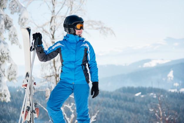 Kobieta narciarz ze sprzętem narciarskim, cieszący się wspaniałą scenerią w górach zimą
