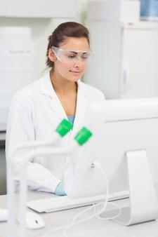 Kobieta naukowca za pomocą komputera w laboratorium