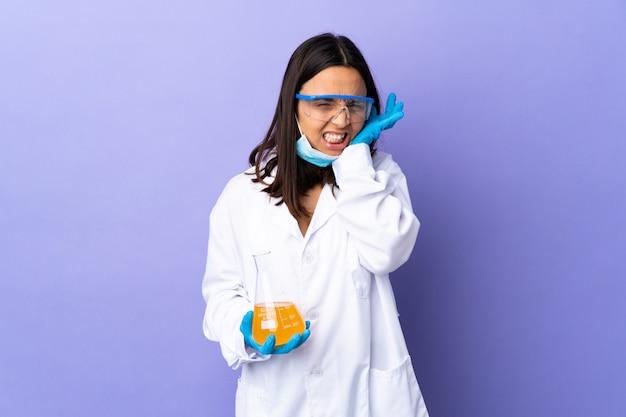 Kobieta naukowiec badająca szczepionkę w celu leczenia udaremnionej choroby i zakrywająca uszy
