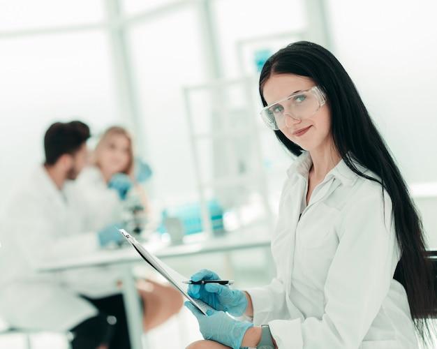 Kobieta naukowiec czytanie notatek w dzienniku laboratoryjnym