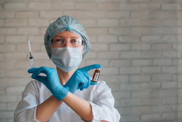 Kobieta naukowiec nosi strój ochronny i maskę trzyma w skrzyżowanych rękach strzykawkę i ampułkę. kobieta lekarz w szpitalu gotowy do zabiegu. badania kliniczne nowej szczepionki na koronawirusa covid 19.