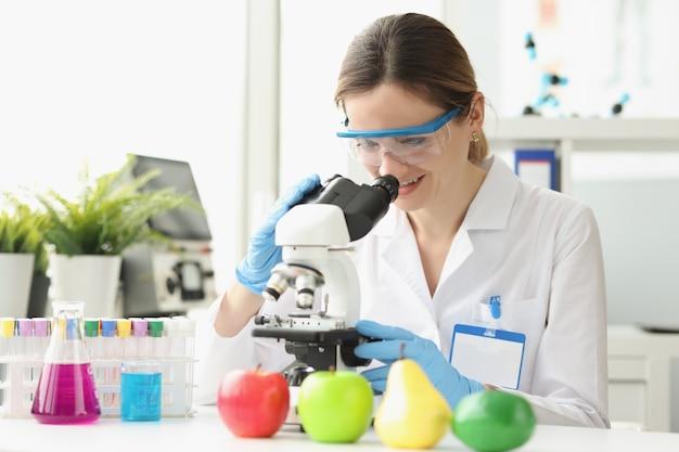 Kobieta naukowiec pracująca na mikroskopie i analizująca plaster miodu owocowego mikrobiologa
