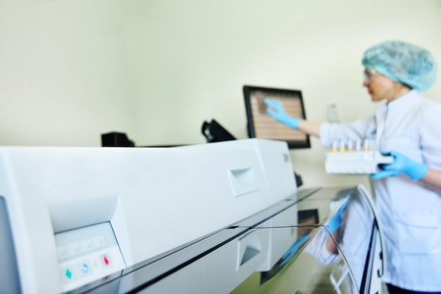 Kobieta naukowiec w pobliżu analizatora w medycznym laboratorium mikrobiologicznym. sprzęt do analizy, dna, pcr