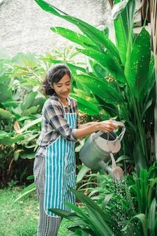 Kobieta nawadnia jej ogród w domu
