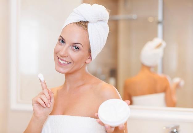 Kobieta nawilżająca twarz po kąpieli