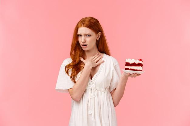 Kobieta nie lubi deseru, wyraża niechęć i rozczarowanie, dotykając szyi jak chętnego wymiotowania