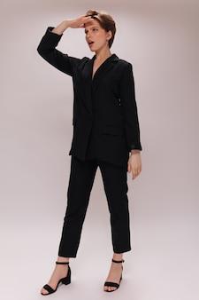 Kobieta nie może się doczekać. portret pani w czarnym stroju na białym tle. krótkowłosa dziewczyna w ciemnym garniturze pozuje na na białym tle