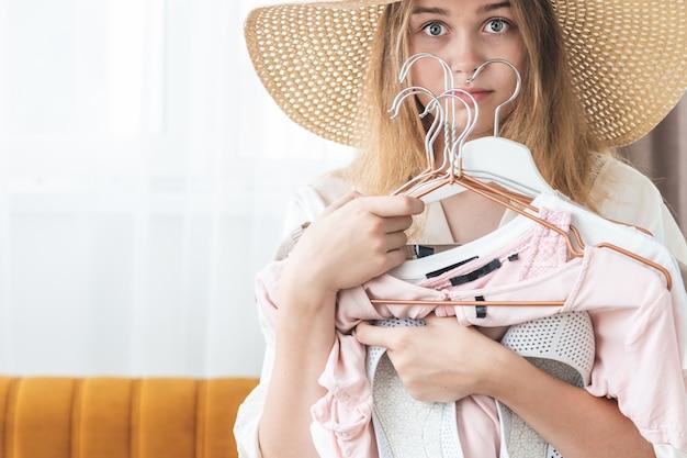 Kobieta nie może wybrać pakietu ubrań na podróż. odziewać, moda, styl i ludzie pojęć, - kobieta wybiera odziewa garderobę w domu.