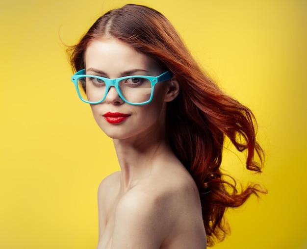 Kobieta niebieskie okulary jasne żółte tło