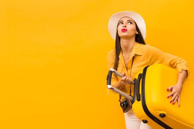 Kobieta niesie ciężkiego wycieczka bagaż z kopii przestrzenią