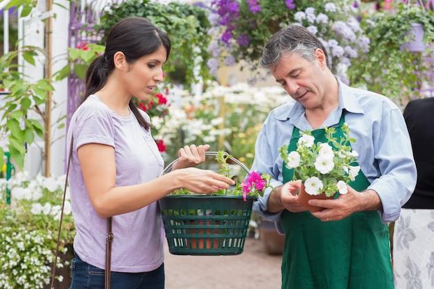 Kobieta niesie kosz podczas gdy kupujący kwitnie i opowiadający pracownik