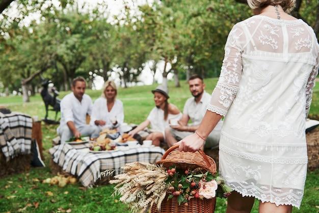 Kobieta niesie kosz z suchymi roślinami. grupa dorosłych przyjaciół odpoczywa i rozmawia na podwórku restauracji w porze kolacji