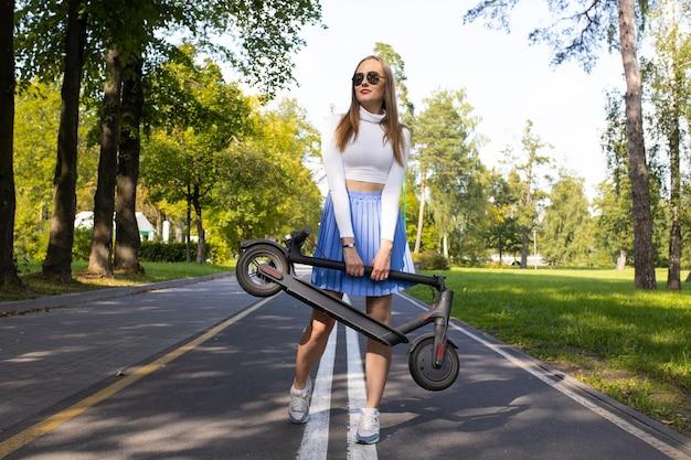 Kobieta niesie po parku złożony skuter elektryczny
