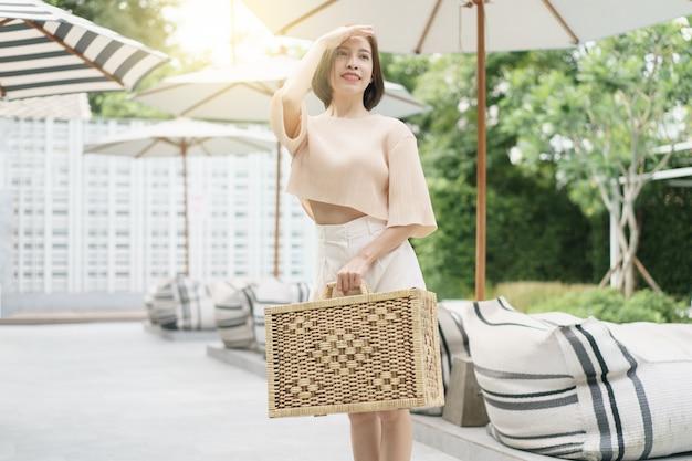 Kobieta niesie wiklinową walizkę. skupić oczy