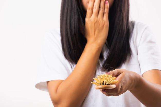 Kobieta nieszczęśliwa problem ze słabymi włosami trzyma szczotkę do włosów z uszkodzonymi, długimi włosami wypadającymi w grzebieniu