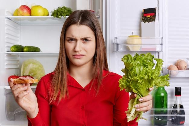 Kobieta niezadowolona marszczy brwi, musi przestrzegać diety, je tylko owoce i warzywa, trzyma w rękach sałatę i kanapkę, stoi w kuchni przy lodówce