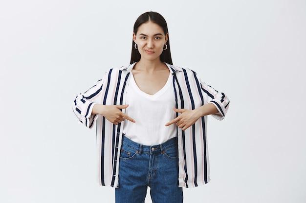 Kobieta niezadowolona ze swojego ciała nie przygotowała się na lato. rozczarowana młoda atrakcyjna kobieta w bluzce w paski, wskazująca na brzuch i marszcząca brwi, wyrażająca niechęć na szarą ścianę