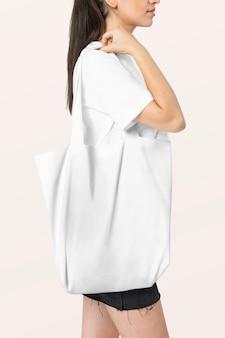 Kobieta niosąca białą torbę na zakupy studio strzelać