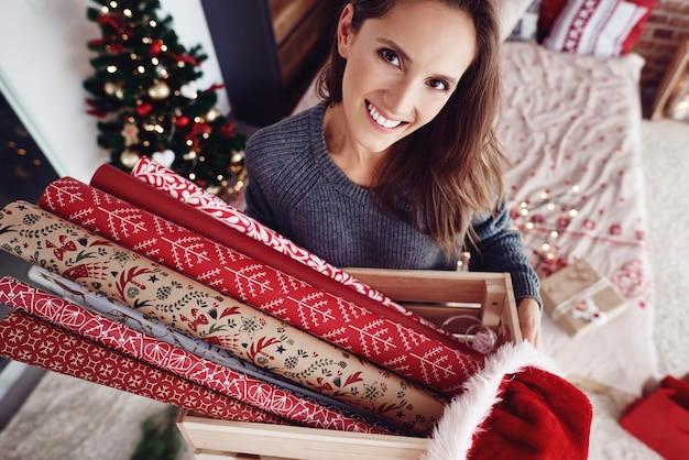Kobieta niosąca drewnianą skrzynię z papierem świątecznym