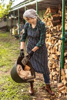 Kobieta niosąca drewno kominkowe