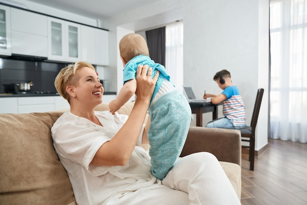 Kobieta niosąca małego synka, podczas gdy najstarszy uczy się w pobliżu