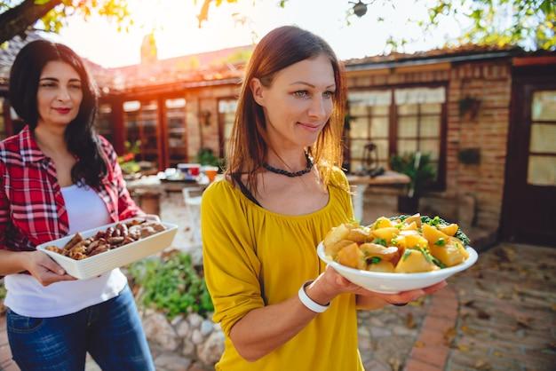 Kobieta niosąca miskę z pieczonymi ziemniakami