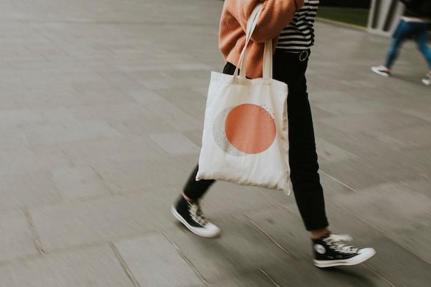 Kobieta niosąca płócienną torbę wielokrotnego użytku