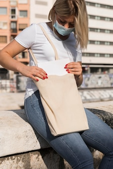 Kobieta niosąca torbę na zakupy i nosząca maskę medyczną