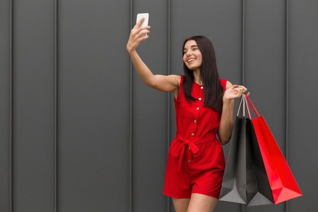 Kobieta niosąca torby na zakupy, biorąc własne zdjęcie