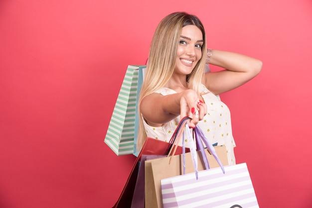 Kobieta niosąca torby na zakupy z happy wypowiedzi.