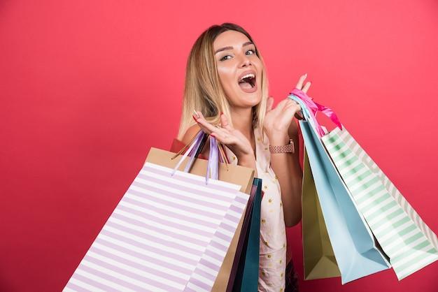Kobieta niosąca torby na zakupy z zaskoczonym wyrazem na czerwonej ścianie.